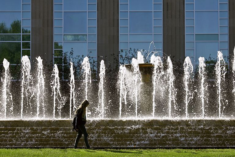 A student walks by the fountain in front of Jacobs School of Music