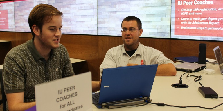 Students working on a laptop at the IU Peer Coaches table in Wells Library.